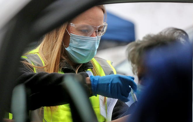 Kelsey Grant gives a COVID-19 vaccination during a drive-thru clinic held at the LeGrand Center in this Star file photo.