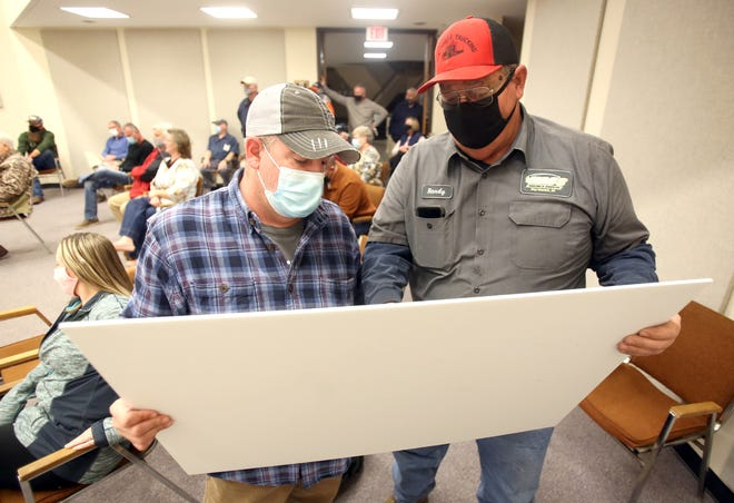 From left, Travis Slycord and Randy McDaniel takes a closer look at plans for a three-phase community off Dixon School Road.
