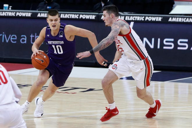 Northwestern's Miller Kopp, left, drives as Ohio State's Kyle Young Wednesday, Jan. 13, 2021, in Columbus, Ohio.