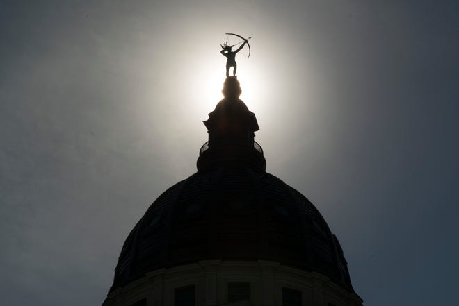 """""""Ad Astra,"""" the bronze statue of a Kansa warrior, is silhouetted atop the dome of the Kansas Statehouse."""
