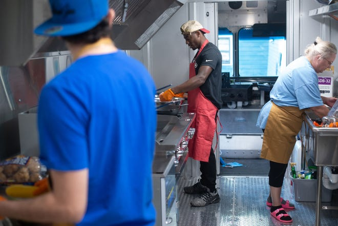 Testing recipes and figuring out all the bells and whistles of their new Flavor Wagon food truck, from right, Deann Owens, Tre'Jor Hopkins and Thomas Flowers work to prepare buffalo chicken sandwiches and salmon quinoa bowls Oct. 1. The latest round of Paycheck Protection Program funding is meant to target small businesses, such as food trucks, that need help staying afloat.