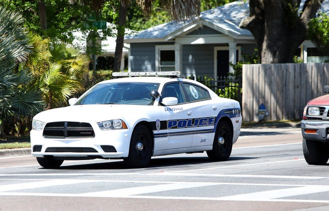 A officer with the Gainesville Police Department drives south on Northwest Sixth Street near GPD headquarters.
