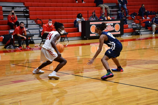 Graham guard Isaiah Lea, left, brings the ball up the court as Reidsville's Amari Badgett defends in a game last week.