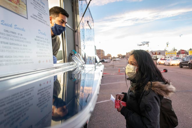 Carol Lara, right, academic program administrator at Parkview Medical Center, places an order with Ulises Flores at the Manny's Mexican Food truck during the first of eight weekly food truck events for Parkview staff on Wednesday January 13, 2021.