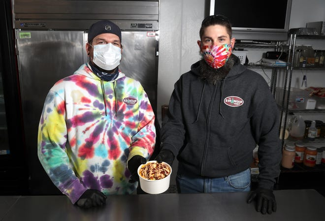 Michael Laughlin (left) Redwood Wagon food truck and catering general manager, and Kyle Hood, co-owner of the business, are shown with one of their Americana bowls Jan. 13 at their prep kitchen in Worthington. Hood and his business partners opened a carryout and delivery service at the prep kitchen in December to help bolster sales in response to losses during the COVID-19 coronavirus pandemic.
