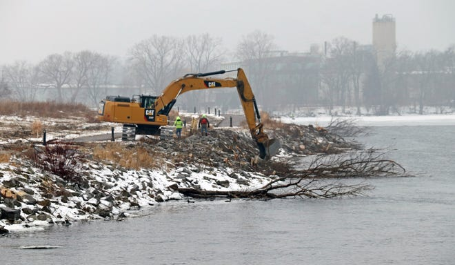 Contractors remove trees along the shore of Arrowhead Park in Neenah. The trees will be strategically placed in the water to serve has a fish habitat.