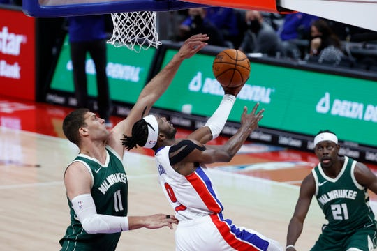 Pistons forward Jerami Grant goes to the basket while being defended by Bucks center Brook Lopez in the first half on Wednesday January 13, 2021 at the Little Caesars Arena.
