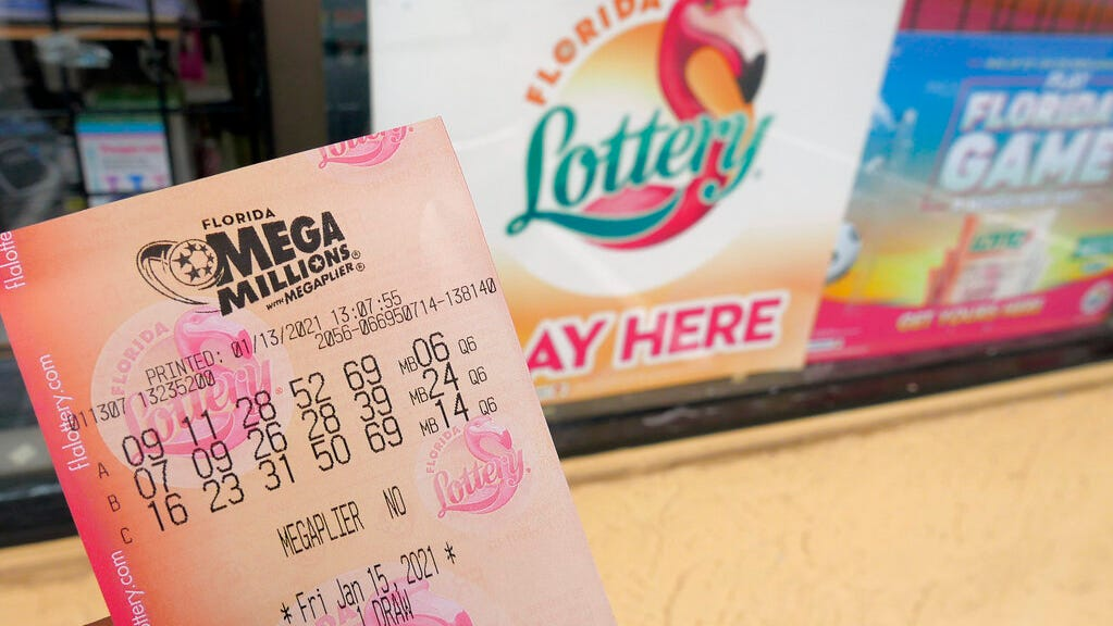 In this Wednesday, Jan. 13, 2021, file photo, a customer shows off a Mega Millions lottery ticket after purchasing it, in Orlando, Fla.