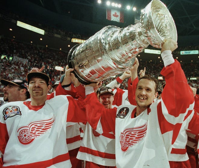 Penyerang Red Wings Tim Taylor, kiri, merayakan dengan Steve Yzerman setelah mengalahkan Flyers 2-1 di Joe Louis Arena untuk memenangkan Piala Stanley pada tahun 1997.