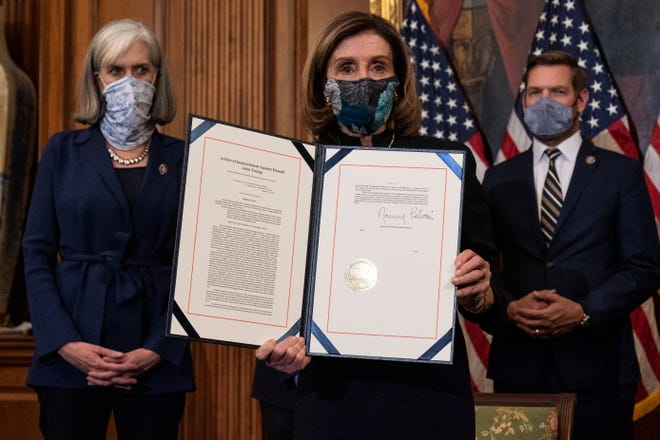 House Speaker Nancy Pelosi of Calif., holds the article of impeachment against President Donald Trump after signing it, in an engrossment ceremony before transmission to the Senate for trial on Capitol Hill, in Washington, Wednesday, Jan. 13, 2021.