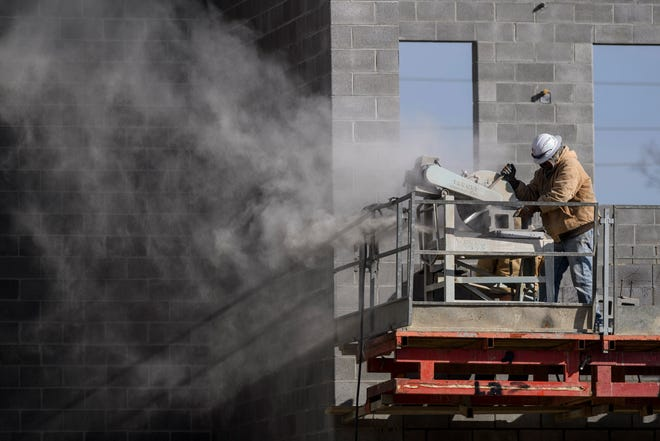 A construction worker cuts concrete blocks while working at the site of the new Jefferson Elementary School building, located behind South Middle School, in Henderson, Ky., Thursday morning, Jan. 14, 2021. A building permit was issued to the Henderson County Board of Education in 2020 for the nearly $17.9 million elementary school construction project, which is expected to be completed during the 2021-22 school year.