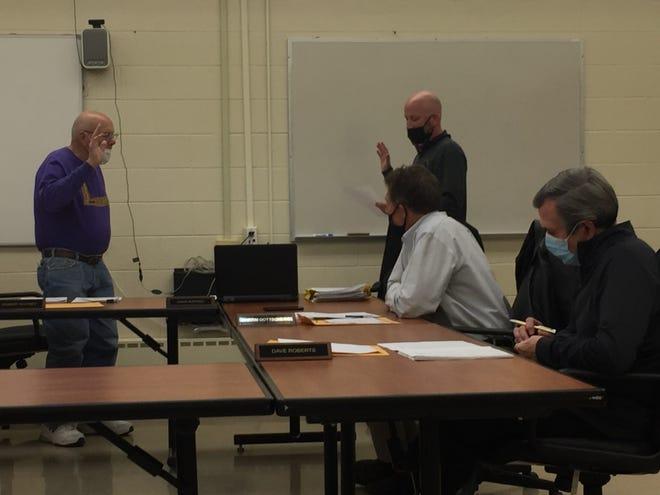 Robert Whitney (l) is sworn in as Lexington school board president by treasurer Jason Whitesel during Wednesday night's meeting.