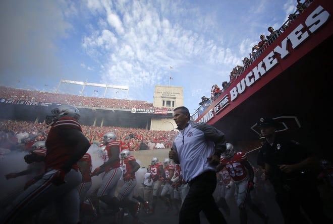 Ohio State Buckeyes head coach Urban Meyer brings his team onto the field before Saturday's NCAA Division I football game against Cincinnati at Ohio Stadium in Columbus on September 27, 2014.
