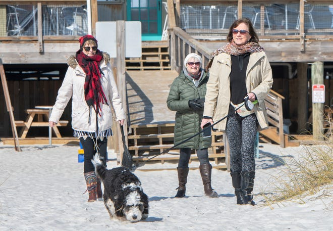 At right, Joyce Decker, of Traverse City, Michigan, walks her dog Zoey along with her sisters Jill Sullivan, left, and Janis Jankowski at Navarre Beach on Wednesday.