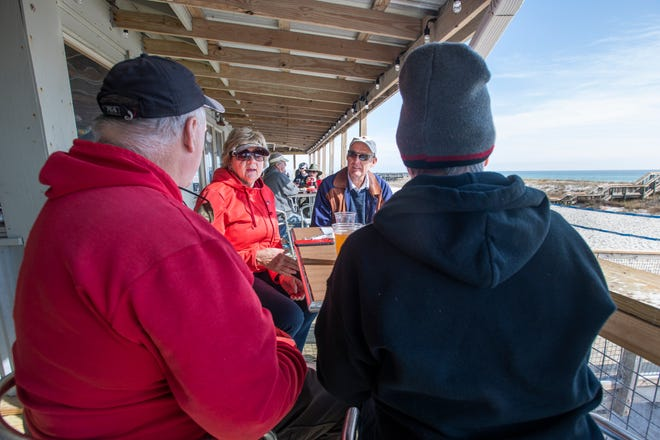 Connie and Paul Reinhardt, of Louisville, Kentucky, and Mike and Cissie Roma, of South Royalton, Vermont, chat Wednesday while having lunch at Windjammers on the Pier overlooking Navarre Beach.