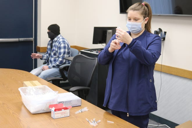 Katie Crowell, director of nursing at the Ottawa County Health Department, draws a dose of the COVID-19 vaccine during a clinic held in Port Clinton on Thursday.