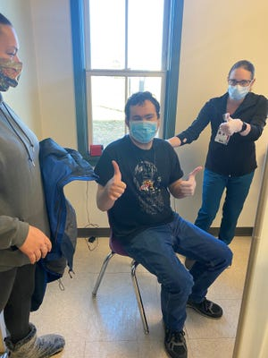 Trey T. gives thumbs-up after receiving a COVID-19 vaccine.  Natalie Haradya of the Anderson Center for Autism staff is on the left and Northern Dutchess Hospital's Christina Watson is on the right.