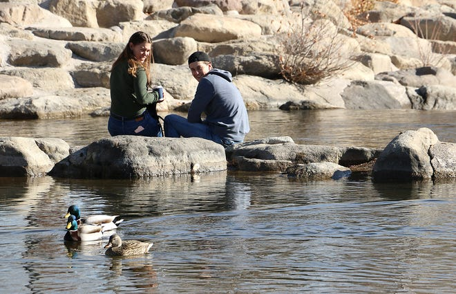 A young couple takes advantage of the warm weather while hanging out on some rocks in the Truckee River in downtown Reno on Jan. 14, 2021.