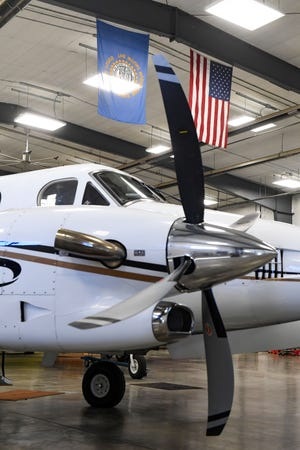 The South Dakota and American flags hang above a plane in the state fleet stand in the hangar on Monday, January 11, at the Pierre Regional Airport.