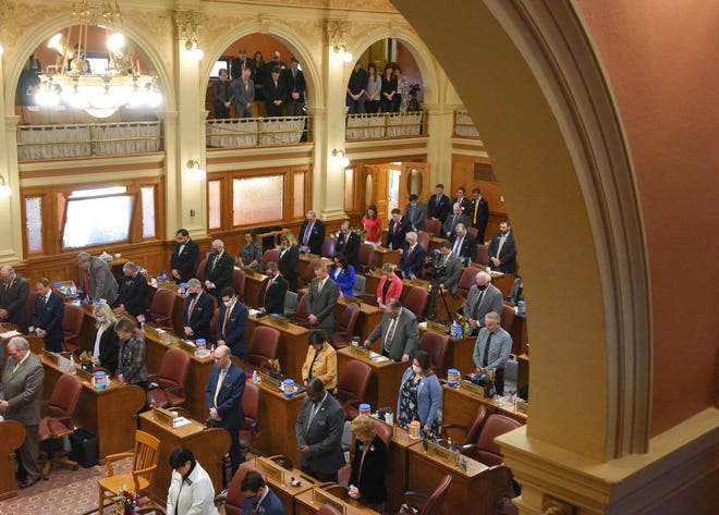 Lawmakers bow their heads during the invocation before the State of the State address on Tuesday, January 12, in the House of Representatives at the South Dakota State Capitol in Pierre.