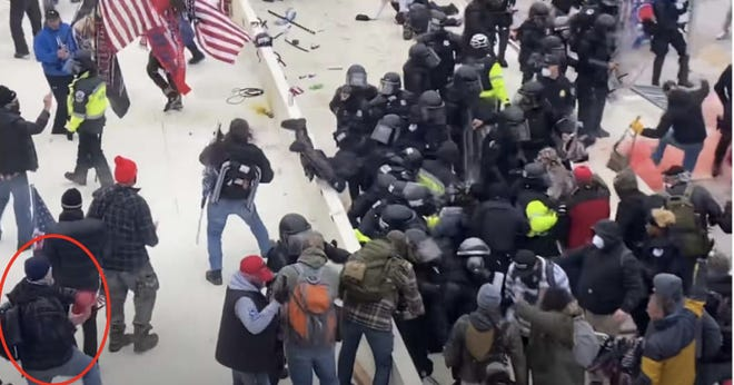 Images from video footage captured at the Jan. 6, 2021, riot at the U.S. Capitol allegedly show retired firefighter Robert Sanford in the crowd and throwing a fire extinguisher at a police officer.