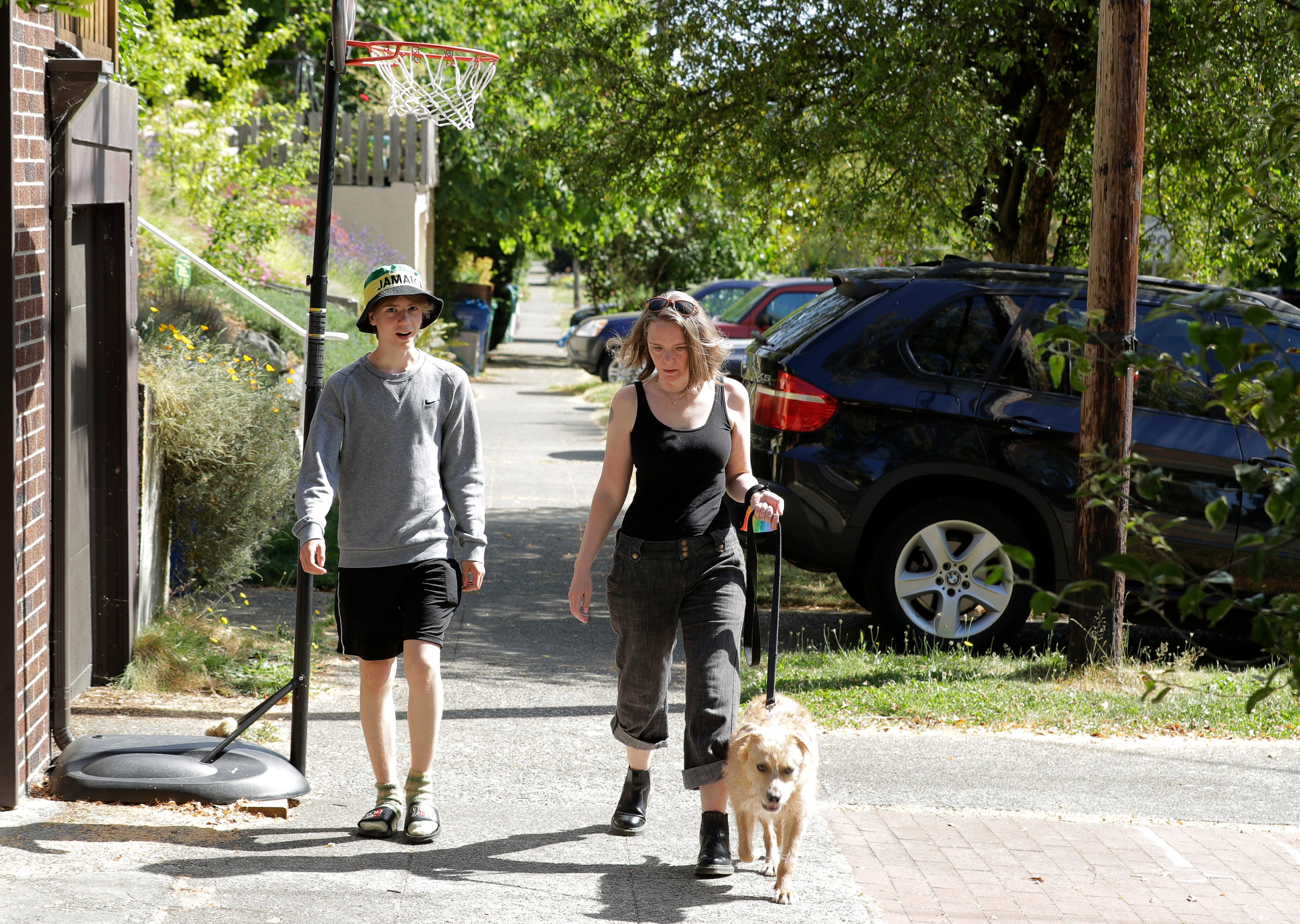 Jennifer Haller, right, the first person to receive a trial dose of a COVID-19 vaccine, walks with her son Hayden, 16, and their dog Meg, Sunday, July 19, 2020, in Seattle. As the world's biggest COVID-19 vaccine study gets underway more than four months after Haller and 44 others became the first participants in a phase-one coronavirus vaccine study that has produced encouraging results, Haller is encouraging other people to sign up for future trials.