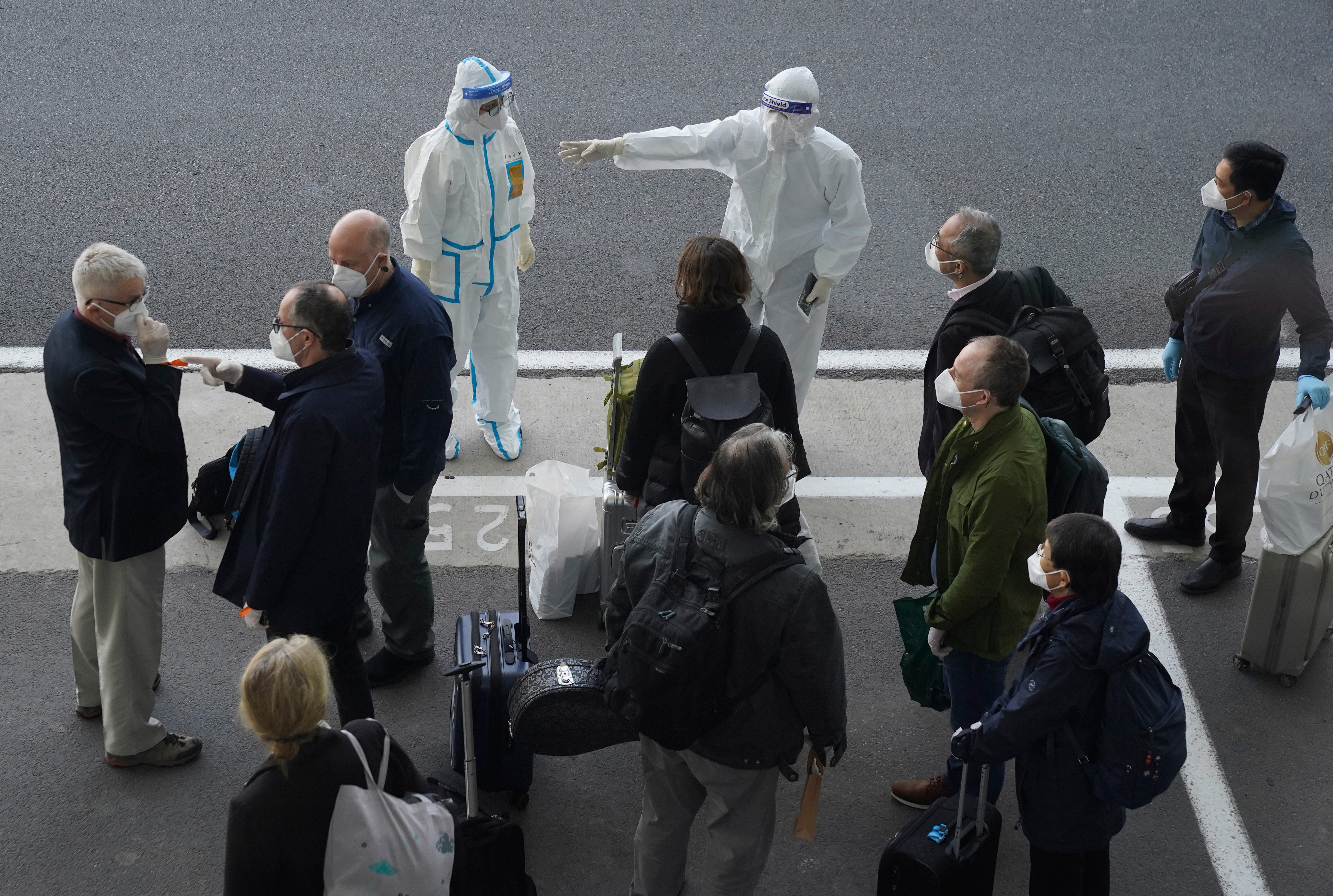 A worker in protective gear directs members of the World Health Organization after their arrival at the airport in Wuhan in central China's Hubei province on Jan. 14. A global team of researchers came to the city where the coronavirus was first detected to investigate its origins amid uncertainty about whether Beijing might try to prevent embarrassing discoveries.