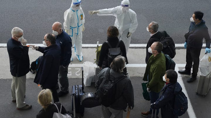 A worker in protective coverings directs members of the World Health Organization (WHO) team on their arrival at the airport in Wuhan in central China's Hubei province on Thursday, Jan. 14, 2021. A global team of researchers arrived Thursday in the Chinese city where the coronavirus pandemic was first detected to conduct a politically sensitive investigation into its origins amid uncertainty about whether Beijing might try to prevent embarrassing discoveries.