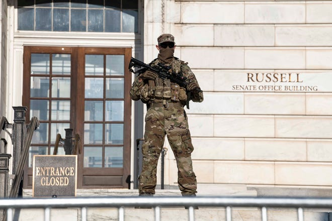 Armed D.C. National Guard troops in Washington, DC help secure buildings and maintain a perimeter around the U.S. Capitol on Jan. 13, 2021.