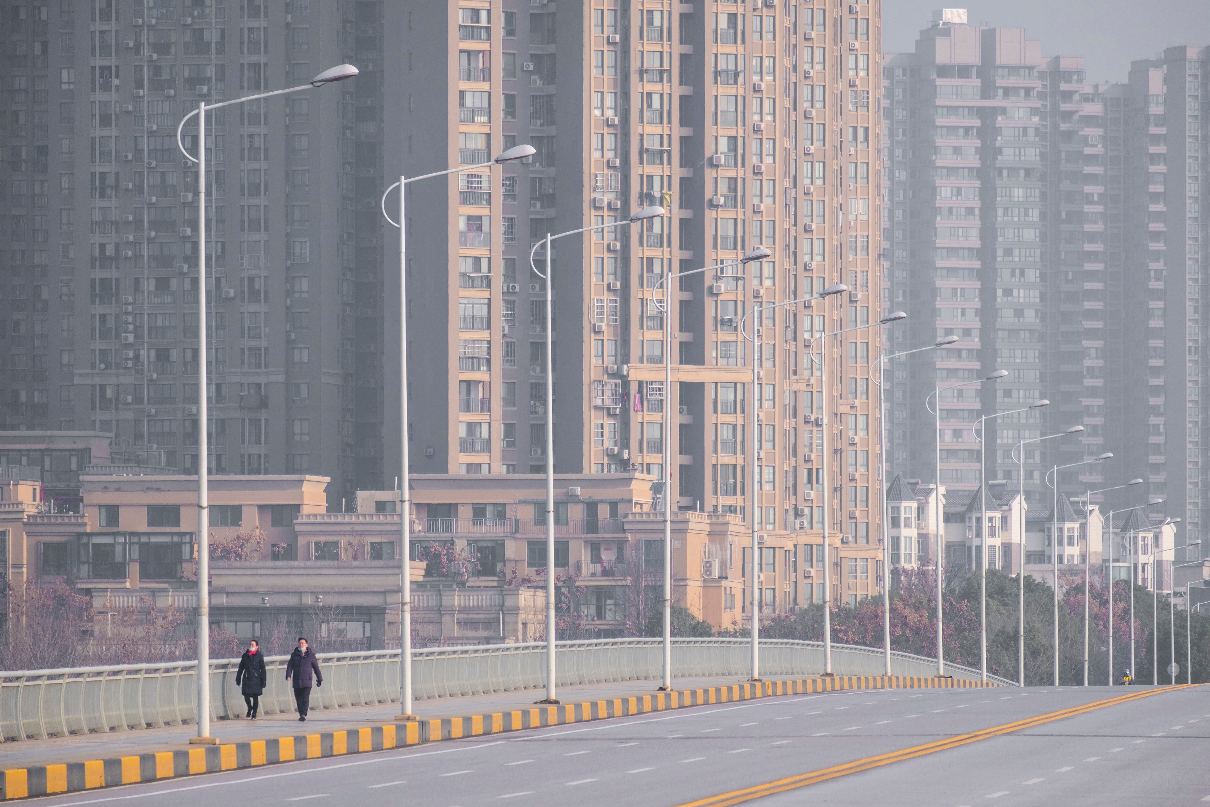 People wear face masks Jan. 28, 2020, when venturing out on the largely deserted streets of Wuhan in central China's Hubei Province.
