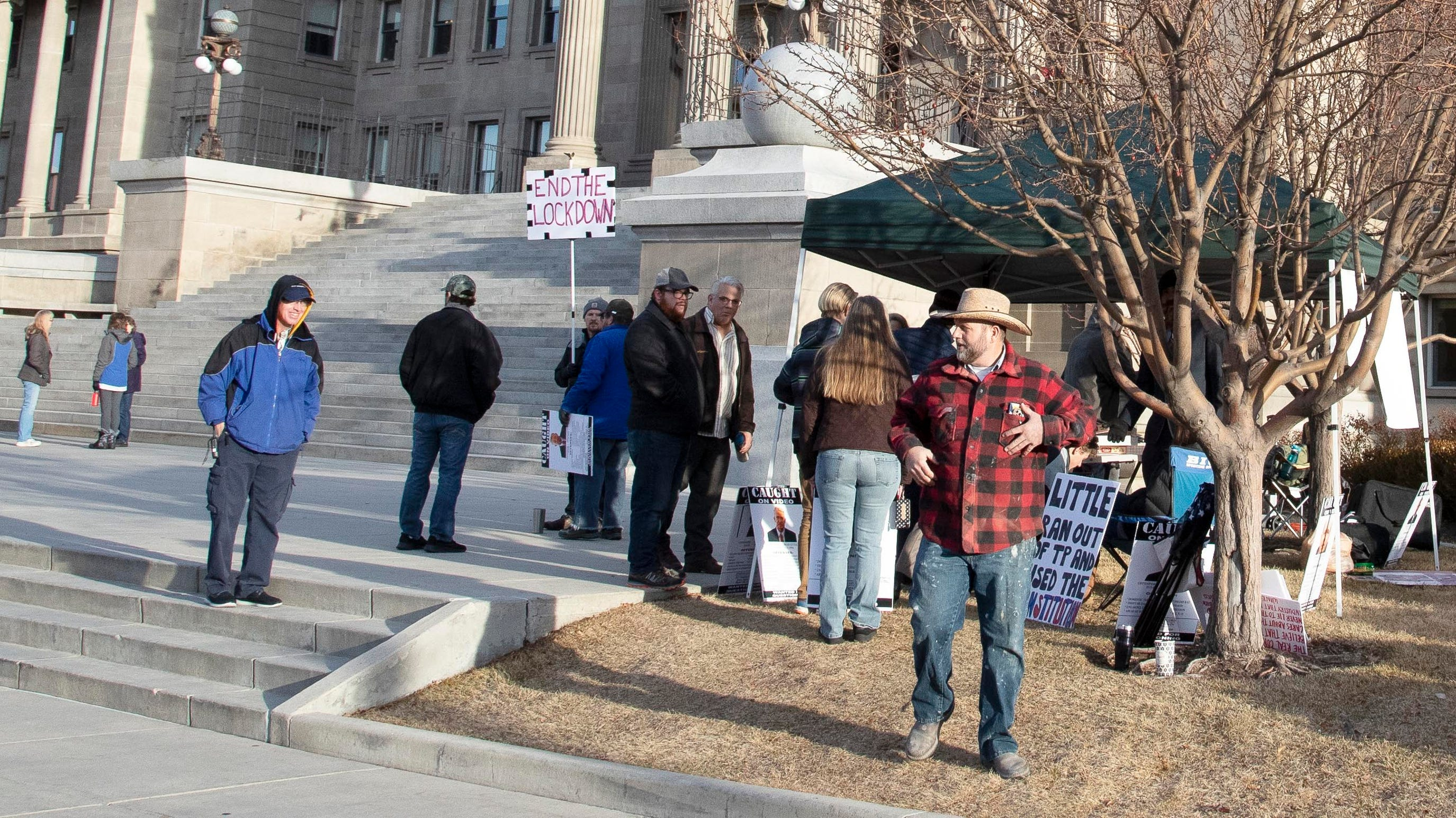 Ammon Bundy, right, arrested twice last summer at the Idaho Capitol, returns Monday, Jan. 11, 2021, to deliver protest signs to demonstrators on the first day of the Idaho Legislature in Boise.