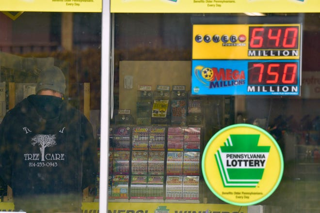 A sign at Conjelko's Dairy Store in Windber, Pa., shows the massive jackpots for Mega Millions and Powerball on Thursday.