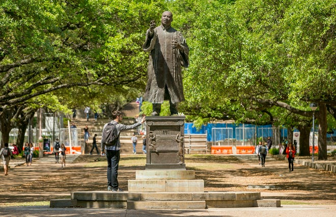 John William Meyer pauses on his way to class at the University of Texas in 2018 to touch the statue of Martin Luther King Jr. on the 50th anniversary of the civil rights leader's 1968 assassination. This year's MLK Day celebrations are going mostly virtual due to the coronavirus pandemic.