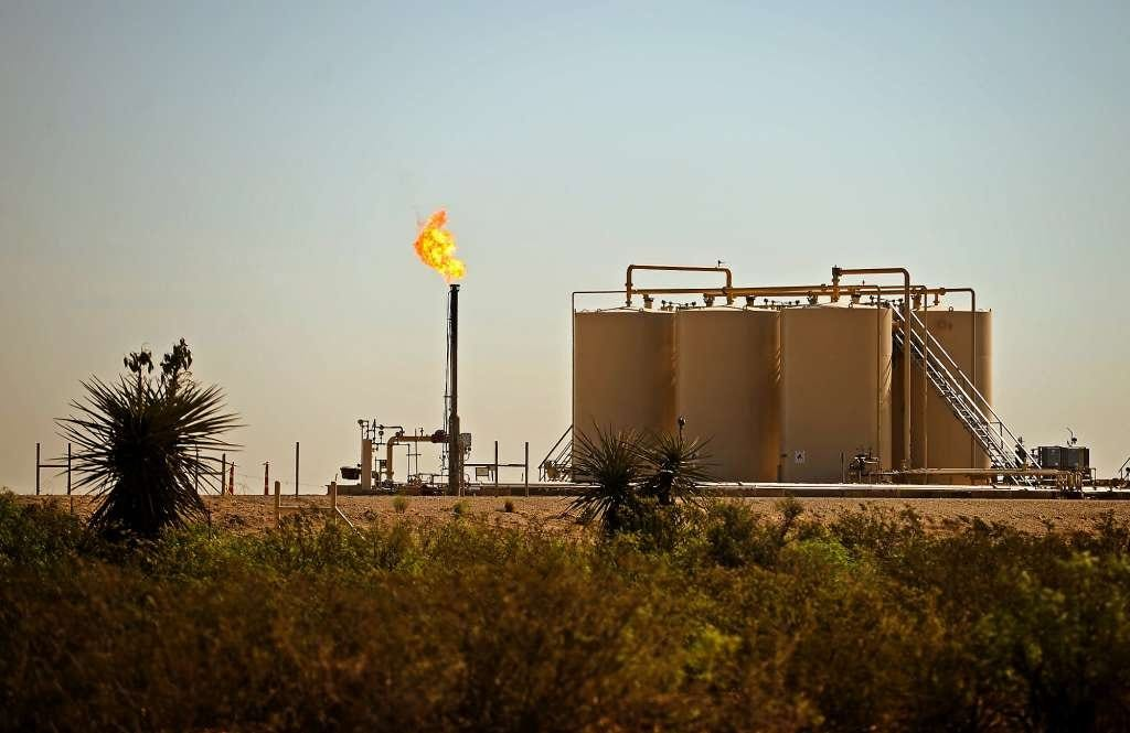 A natural gas flare burns near storage tanks in Reeves County in West Texas.