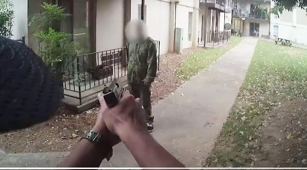An officer points a gun at Salvador Salazar, who is outside an apartment complex and holding a machete. [Athens-Clarke police video photo]