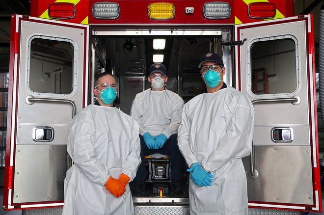 Lt. Matt Schneider, left, Dave McLain, center, and Dan Stehler stand in full personal protection gear that is worn while out on calls, Friday, Jan. 15, 2021, in Stow, Ohio. Since the beginning of the pandemic, only 10 personnel have tested positive for the virus. [Jeff Lange/Beacon Journal]