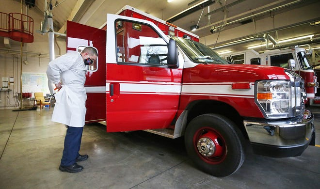 Lt. Matt Schneider gets suited up in PPE at the Stow Fire Station, Friday, Jan. 15, 2021, in Stow, Ohio. [Jeff Lange/Beacon Journal]