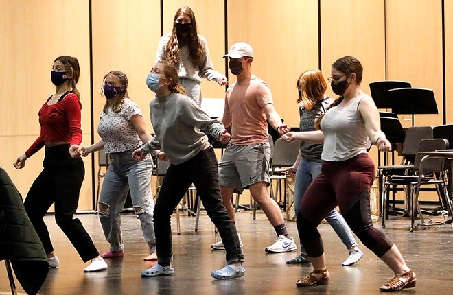 """Sierra Williams, on chair, along with Maiyah Lewis, Eleanor Merkel, Caylie Kubasek, Aidan Chandler, Grace Zeigler and Rachel Robison rehearse a number on the stage of Archer Auditorium for the upcoming musical """"Godspell."""""""