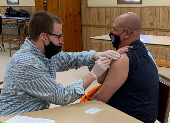 Bob Gwin, pharmacist with Hometown Pharmacy, administers the Moderna COVID-19 vaccine to Chad Angiolelli, volunteer firefighter with Union Township, last month at the fire hall. All Lawrence County emergency and first responders were able to receive a free vaccine.