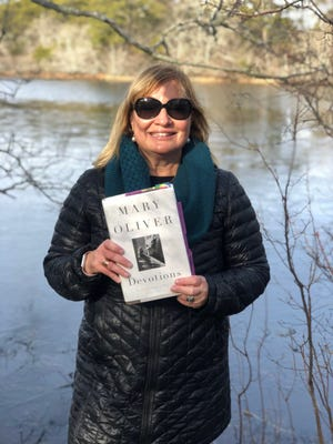 Andrea Brandeis, standing on New Year's Day 2021 at Cape Cod National Seashore, on the Beech Forest trail in front of Mary Oliver's beloved Blackwater Pond.  Brandeis will present an introduction to the Provincetown poet's life and work at Titcomb's Bookshop, via Zoom, on Thursday. (COURTESY OF ANDREA BRANDEIS)