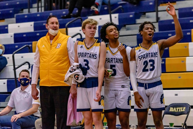 Battle head boys basketball coach Brian Meny, left, watches from the sideline with seniors Tristan Meny (3), Cachao Gianquinto (5) and Isaiah Johnson (23) in the final moments of the Spartans' 75-37 victory over Marshall on Thursday night at Battle High School.