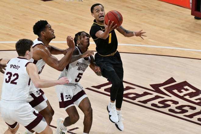 Missouri guard Xavier Pinson (1) goes up for a shot while defended by Mississippi State guard Deivon Smith (5) during a game Jan. 5 at Humphrey Coliseum in Starkville, Miss.