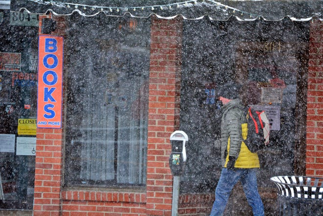 A pedestrian contends with wet snow in downtown Columbia on Friday .