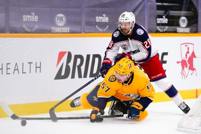 Predators defenseman Dante Fabbro (57) and the Blue Jackets' Oliver Bjorkstrand (28) battle for the puck in the first period of the season-opener for both teams Thursday night in Nashville, Tenn. (AP Photo/Mark Humphrey)