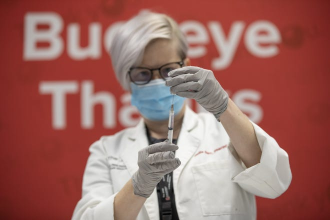 Ohio State University pharmacist Hallie Barr prepares doses of the Pfizer COVID-19 vaccine as university medical center employees receive their first dose at the Schottenstein Center in Columbus on Friday.