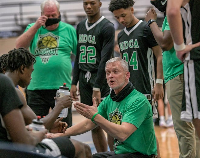 Mount Dora Christian Academy head coach Steven Hayes talks with his players during a timeout against Oviedo on Jan. 9 at the Nathan Hayes Shootout in Mount Dora. In his 20th season as coach, Hayes has directed the Bulldogs to more than 400 wins. [PAUL RYAN / CORRESPONDENT]