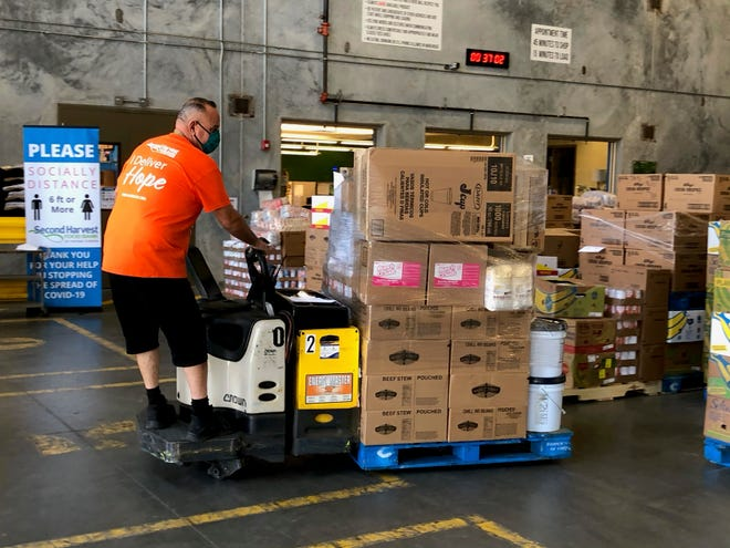 A volunteer loads food for distribution at the Second Harvest warehouse in Orlando.