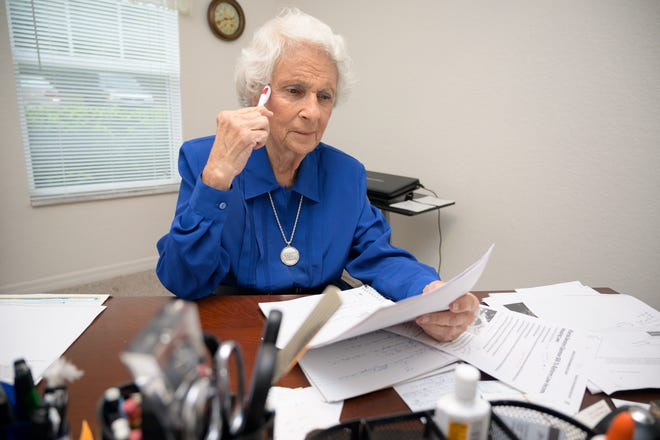 Marie Wissler goes over supporting documents at her home at Silver Pointe Apartments in Leesburg. [Cindy Peterson/Correspondent]