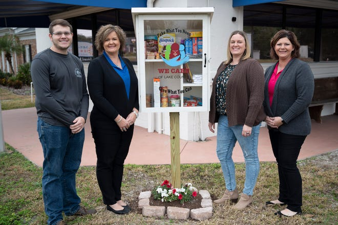 """Workers at We Care of Lake County stand next to their """"Little Free Pantry"""" which is available 24/7 for anyone in need and is stocked with items such as non-perishable food, toiletries, pet food, masks and other necessities. [Cindy Peterson/Correspondent]"""
