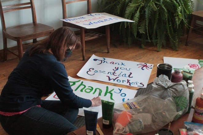 Alicia Amato works on painting signs for the car parade hosted by the Rotary Club of Cambridge to show their appreciation for essential workers.